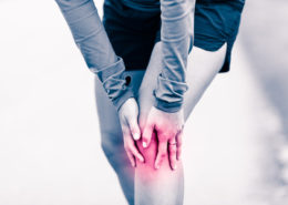 47866085 - runners knee leg pain, woman holding sore and overtrained painful knee, sprain or cramp ache filled with red pink bright place. overtraining injured person when exercising or running outdoors.